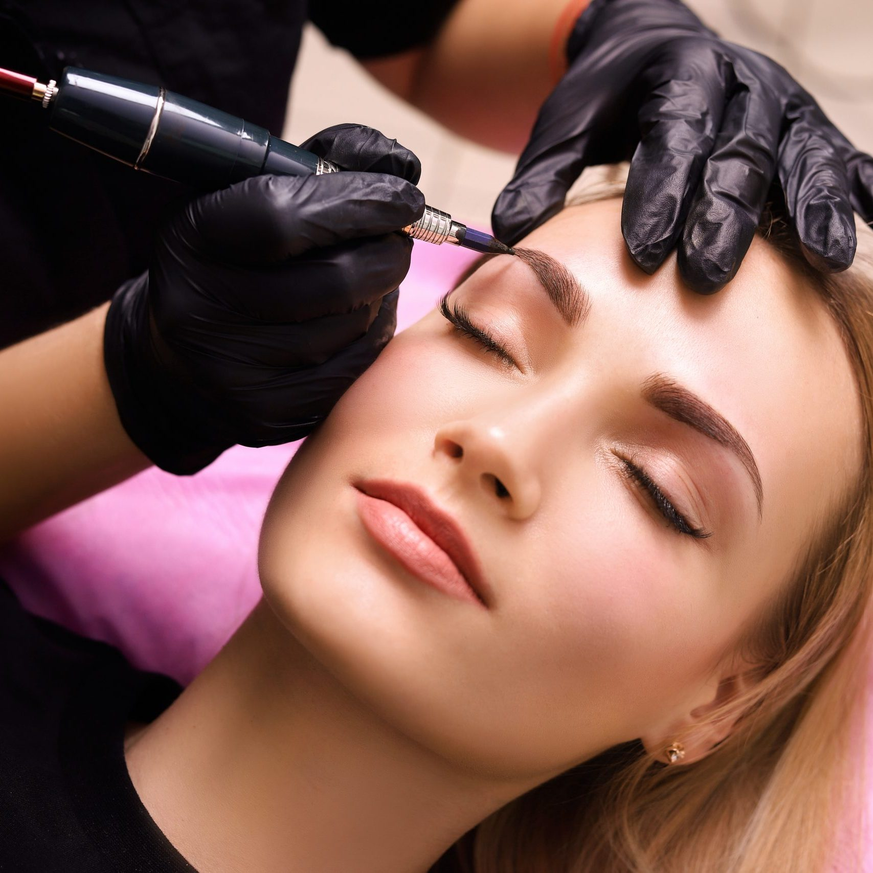 Cosmetologist applying permanent make up on eyebrows- eyebrow tattoo.
